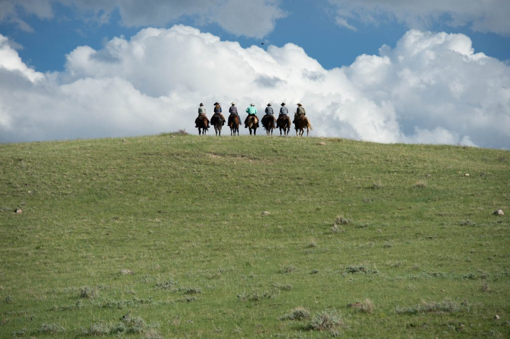 Weaver Leather Endorsee, Ken McNabb and team weaver members ride off into the distance.